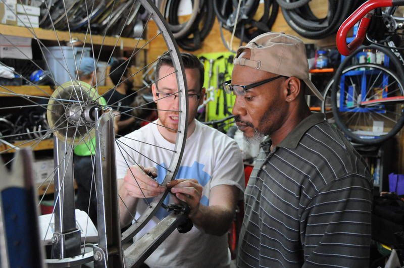 A picture of two men working on a bike wheel.