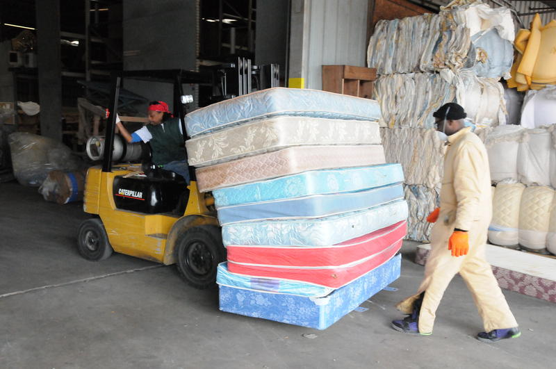 A picture of workers moving a stack of mattresses.