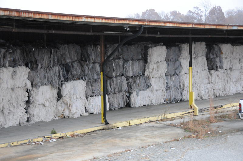 A picture of bales of used materials stacked outside the warehouse.