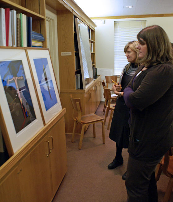 Image of Chapman studying art with two students in the print study room of the Ackland Art Museum.