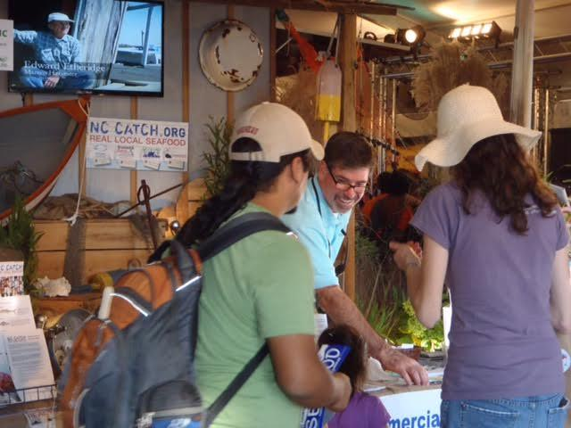 Image of John Aydlett showing a local seafood exhibit at the State Fair.