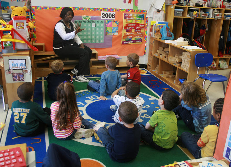 Small children seated on the floor in front of a teacher.