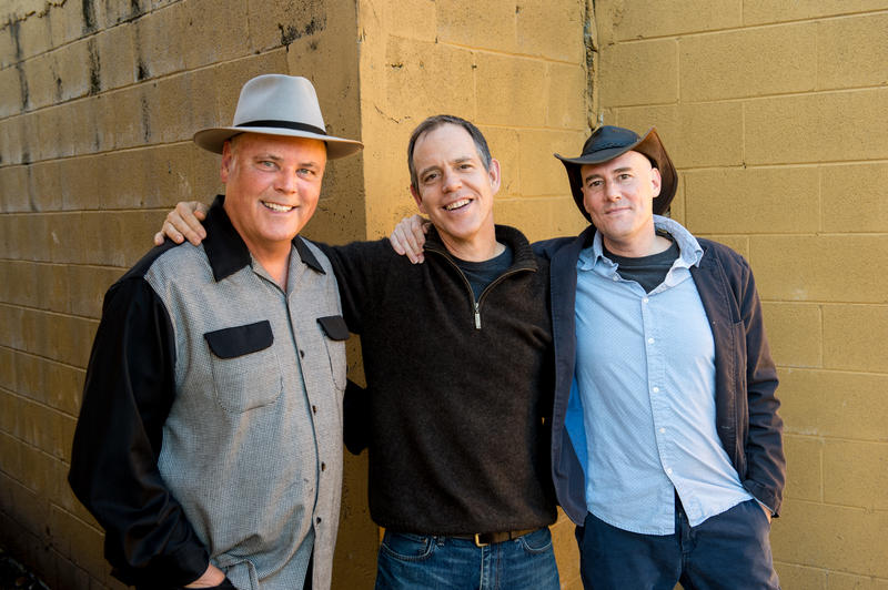 Image of the Three Davids standing and smiling. David Holt (left) is a four-time Grammy winner, David Wilcox (middle) is a well known singer-songwriter and David LaMotte (right) is an author, speaker and peacemaker in addition to being a musician.