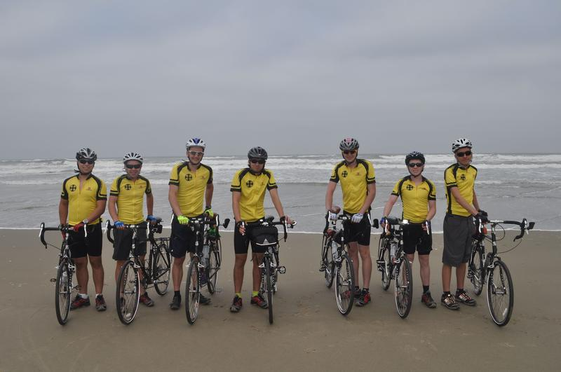 An image of bikers starting a cross-country journey at the Pacific Ocean