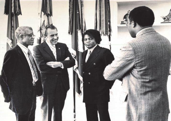 Image of Robert Brown talking with President Nixon, James Brown and his father at the White House.