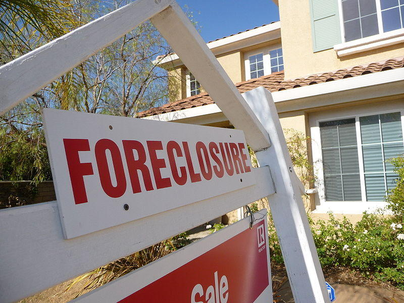 A picture of a foreclosure sign in front of a house.