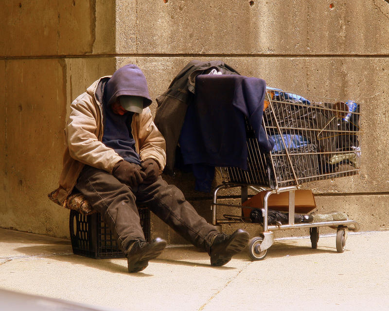 A picture of a homeless man and a shopping cart.