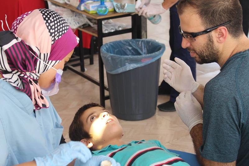 Dr. Sarah Arif of Cleveland and Farris Barakat help a boy at the temporary Syrian American Medical Society dental clinic at the Al-Salaam School in Reyhanli.