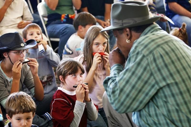 An image of young kids learning to play the harmonica