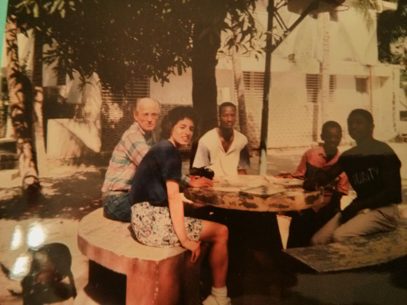 Melissa Radcl is sitting with a board member and some students in the courtyard of a school and orphanage in Haiti. She visited the school with two board members who were based in Providence, Rhode Island where she was living at the time in December 1992.