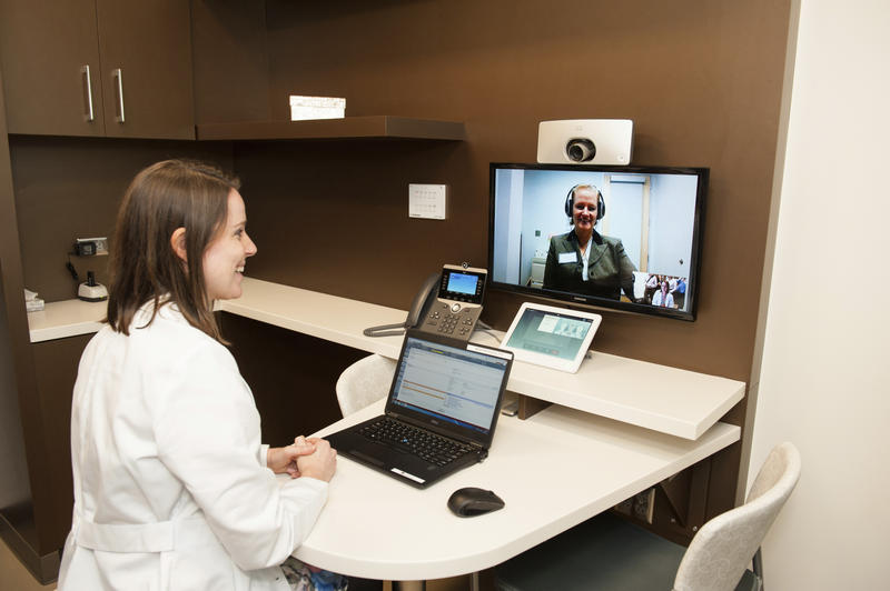 A picture of a patient and a doctor meeting over a web connection.