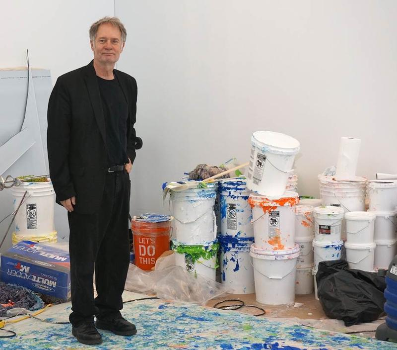 Martiny standing in his WTC work space with 5-gallon buckets of paint.