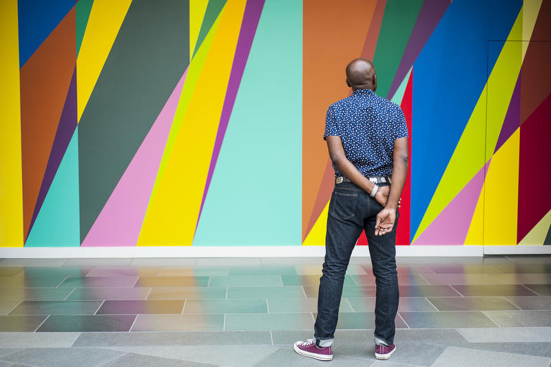 Odili Donald Odita stands in front of his mural, a public art display at the Nasher Museum of Art.