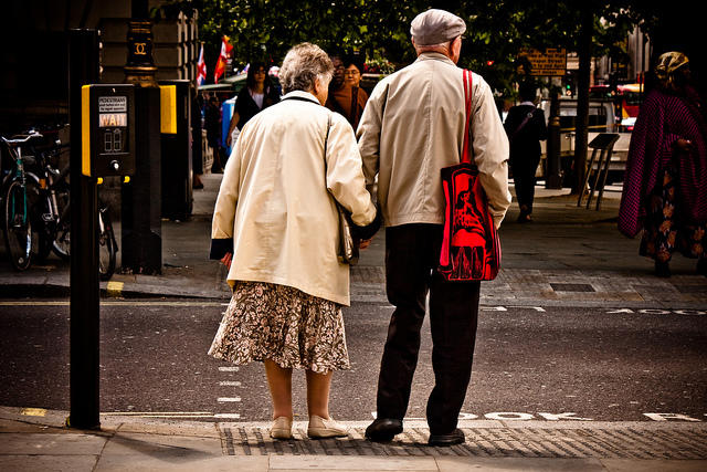 A picture of an elderly couple holding hands.