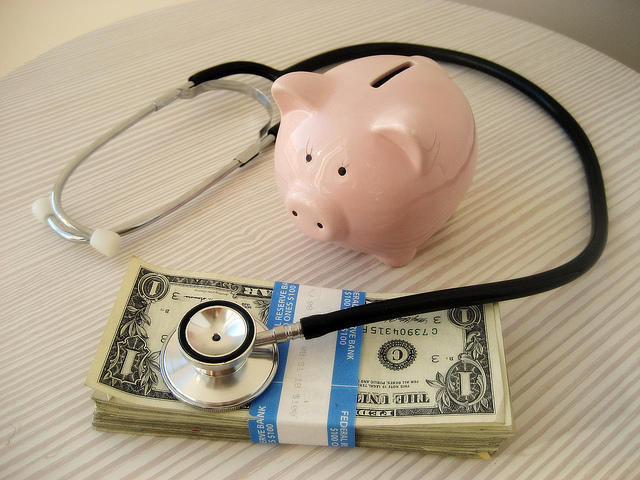 A picture of a stack of cash, a stethoscope and a piggy bank.