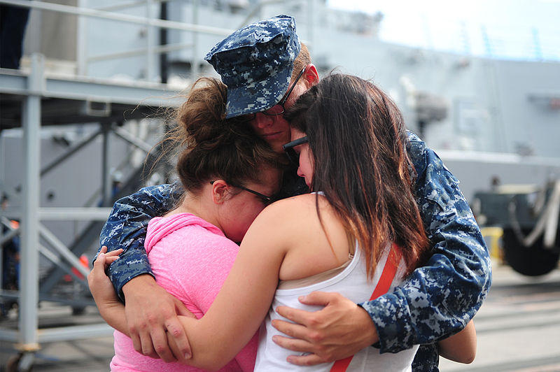 A sailor embraces family and friends before leaving Joint Base Pearl Harbor-Hickam, Hawaii, for an independent deployment to the western Pacific Ocean