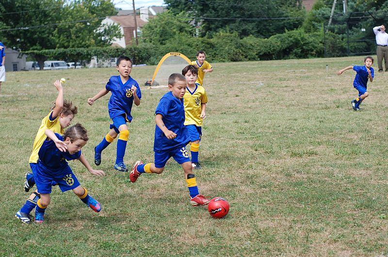 "Eight year old kids play soccer match organized as a part of Fairfax Police Youth Club"" Soccer League."