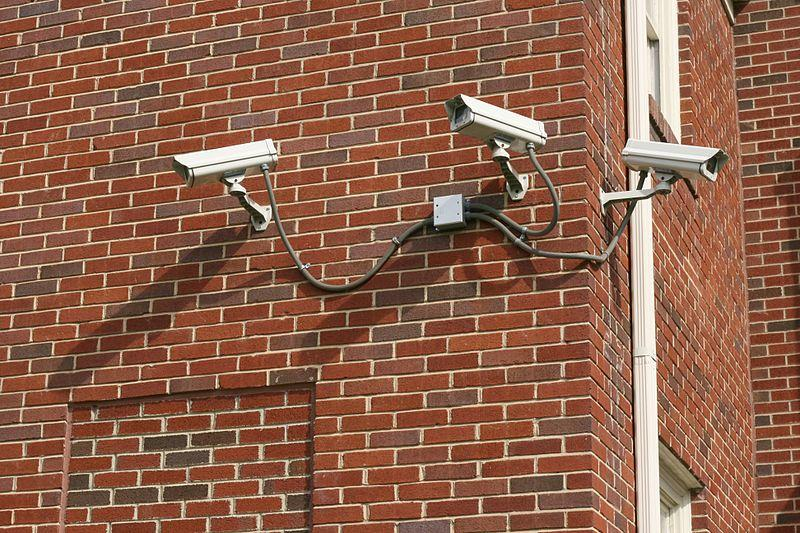 A set of three security cameras on the side of a church all pointing in the wrong direction in Durham, North Carolina.