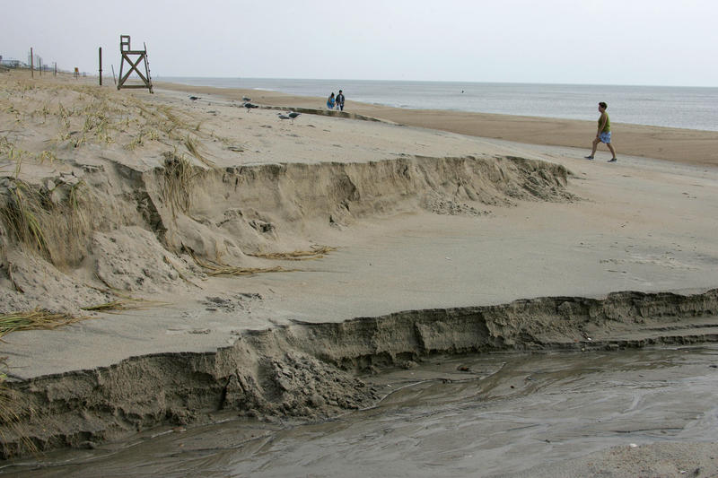 People walk past erosion on the beach caused by Hurricane Ophelia on Kure Beach, N.C. in 2005.