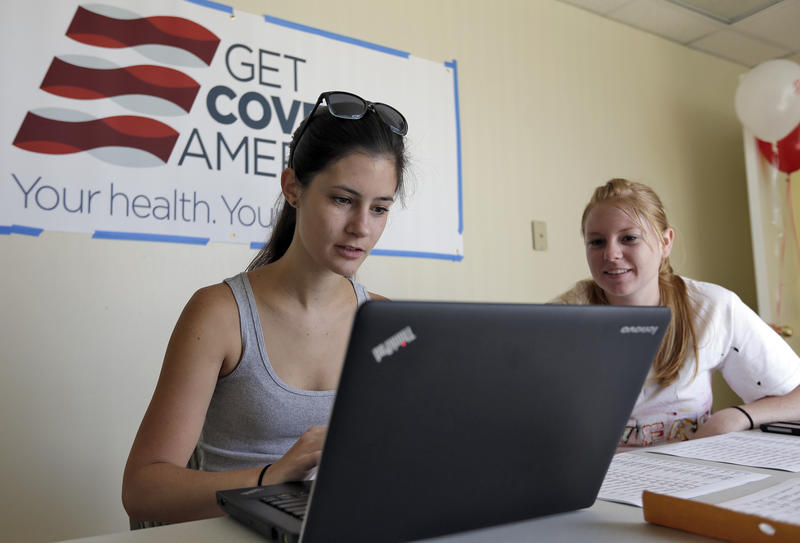Ashley Hentze, left, of Lakeland, Fla., gets help signing up for the Affordable Care Act from Kristen Nash, a volunteer with Enroll America, a private, non-profit organization running a grassroots campaign to encourage people to sign up for health care, T