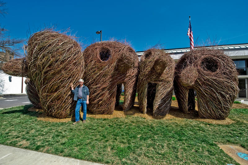 Photo of Internationally-renowned environmental artist Patrick Dougherty with one of his sculptures in South Carolina.