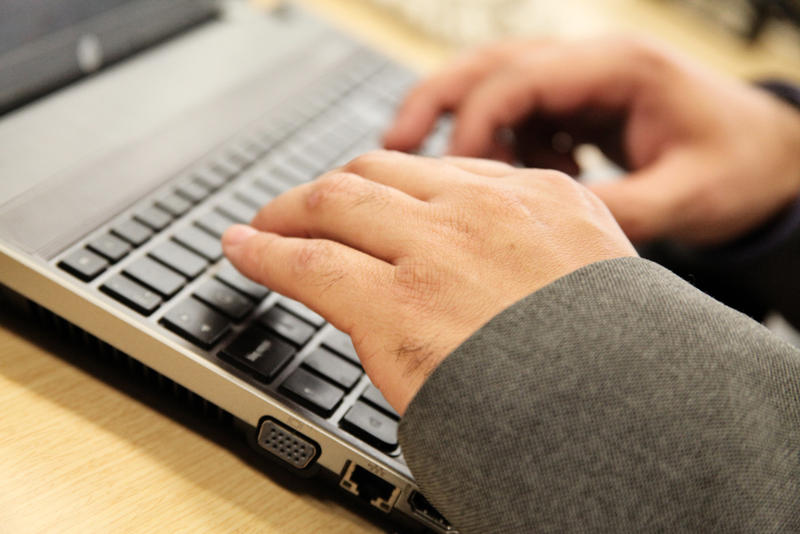 Image of hands typing on laptop
