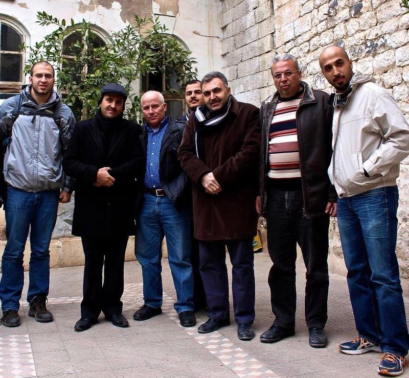 An image of Farris Barakat (far left) and Mike Mallah (far right) with Syrian refugees.