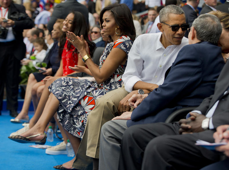 First lady Michelle Obama, center, applauds during player introductions as she attends an exhibition baseball game between the Tampa Bay Rays and the Cuban National team with President Barack Obama and Cuban President Raul Castro.