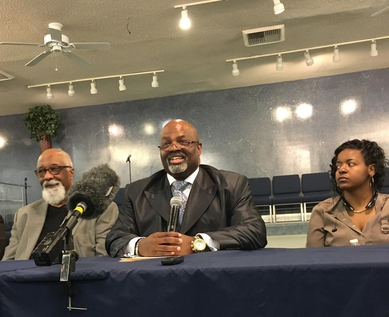 Photo: Bishop Darnell Dickson (center) of Bible Way Temple says neighbors have reacted in silent protest to the shooting of Akiel Denkins. Irv Joyner (left) of the NC-NAACP says he is helping attorney Priscilla McKoy independently investigate the shooting