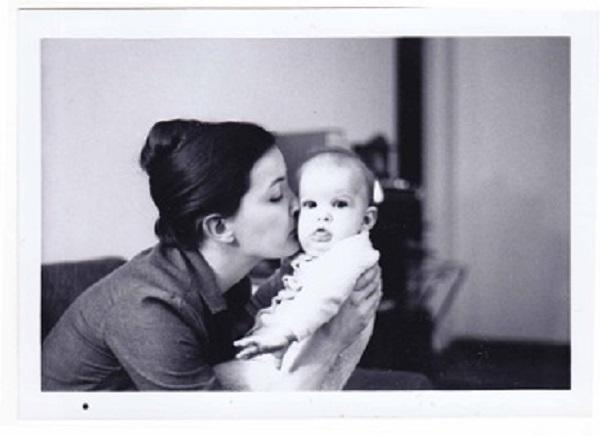 Image of Kate Bowler kissed by her mom when she was a kid.
