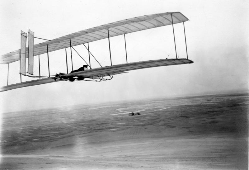 An image of  Wilbur takes wing in the 1902 glider soon after the brothers' return to Kitty Hawk in 1903. Their camp and shed stand alone in the distant wind-swept sands.