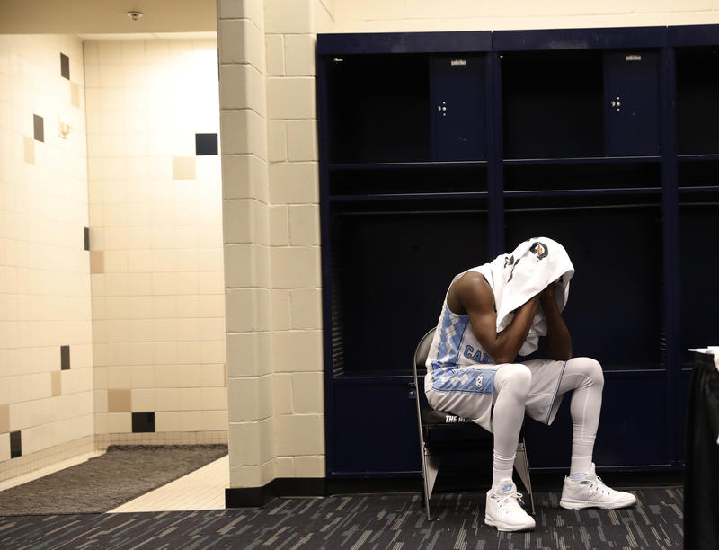 North Carolina's Theo Pinson sits in the locker room after the NCAA Final Four tournament college basketball championship game against Villanova, Monday, April 4, 2016, in Houston. Villanova won 77-74.