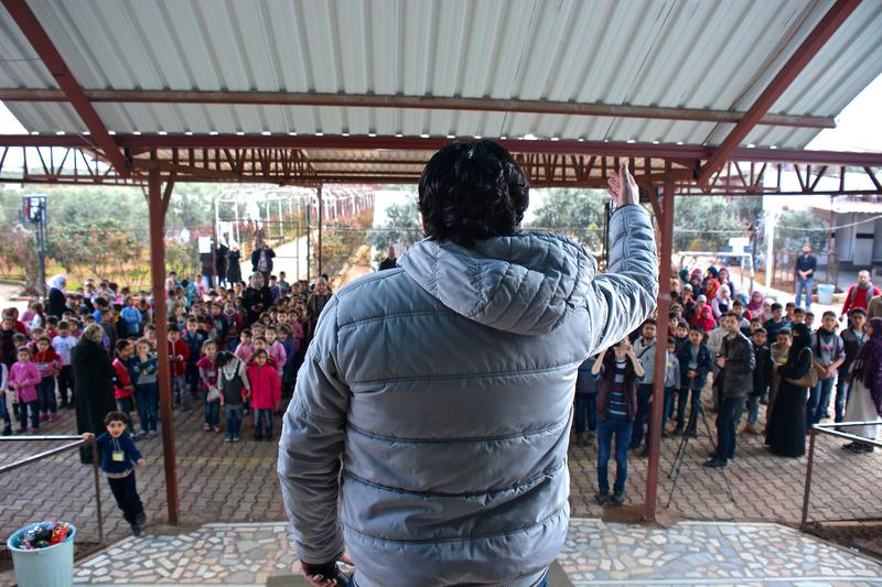 Syrian singer performing for rows of young refugee children at school in Reyhanli.