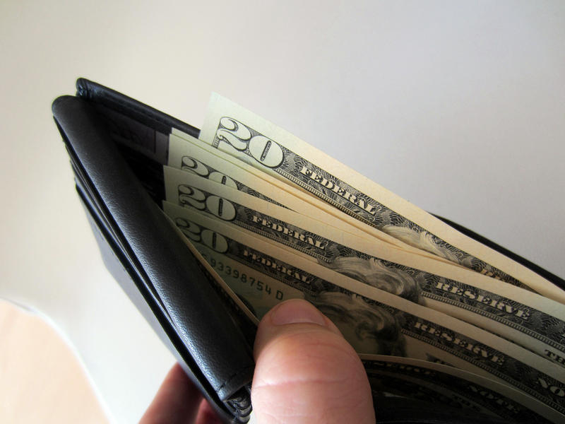 A picture of a wallet with cash in it.