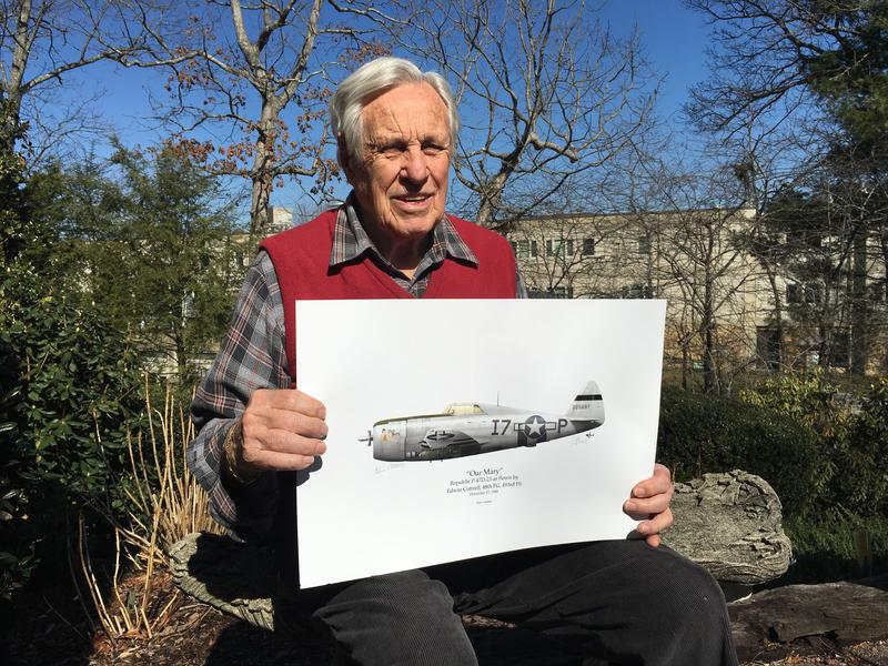 Edwin Cottrell holds an illustration of the P-47D fighter plane he flew in World War II.
