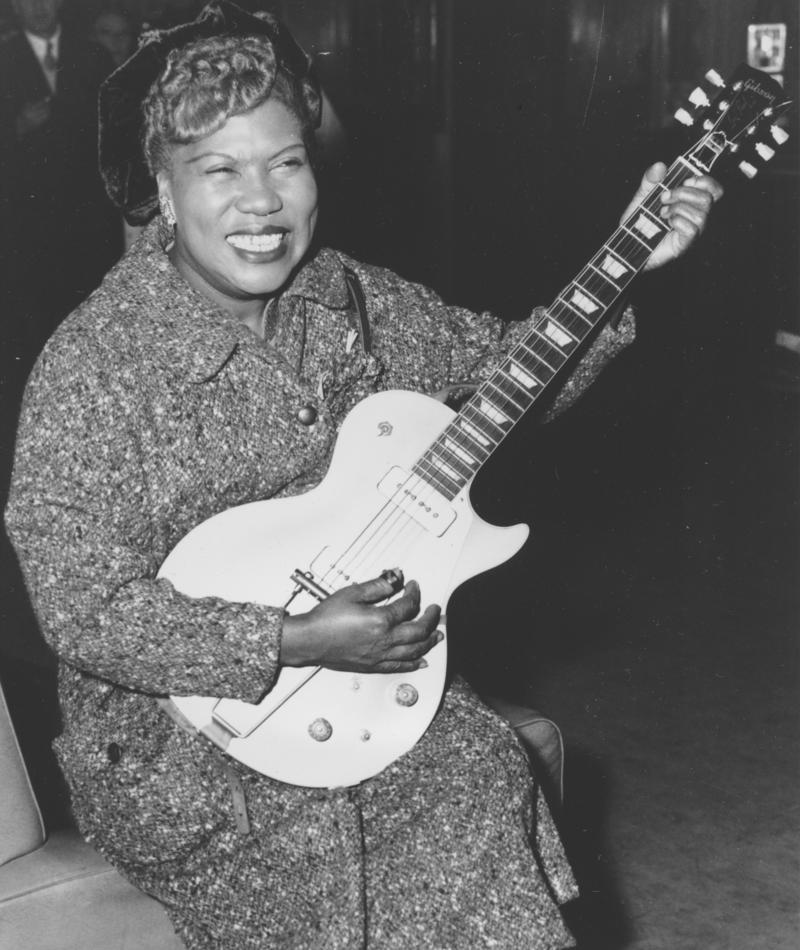 Sister Rosetta Tharpe, guitar-playing American gospel singer, gives an inpromptu performance in a lounge at London Airport, following her arrival from New York on November 21, 1957.