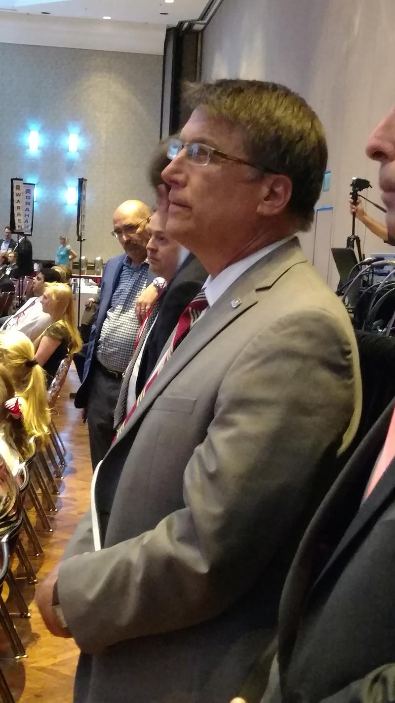 Governor Pat McCrory watching his own re-election video, moments before addressing the crowd. Afterward, he snuck out a service door, avoiding a group of waiting reporters.