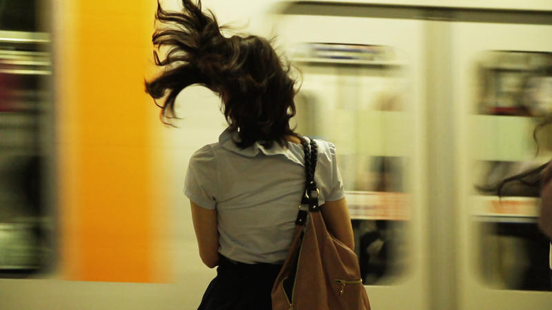 Film Still: A girl awaits her train on a Tokyo subway platform. Tokyo is home to the world's busiest metro system, with approximately 8.7 million daily riders.