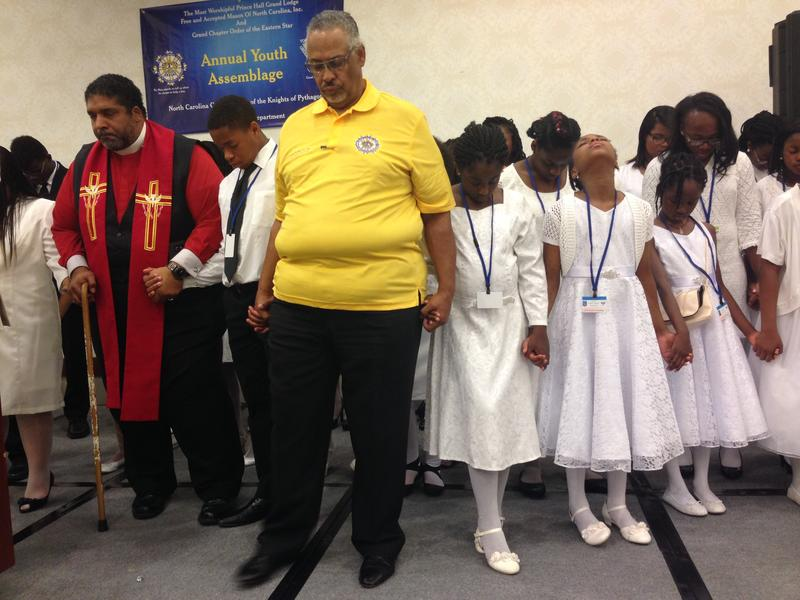 NC NAACP President Rev. William Barber, left, and Ervin Farmer Jr., Grand Knight Director for the Eastern and Coastal Region of The Prince Hall Masons, bow their heads in prayers with children to honor the victims of recent police shootings.