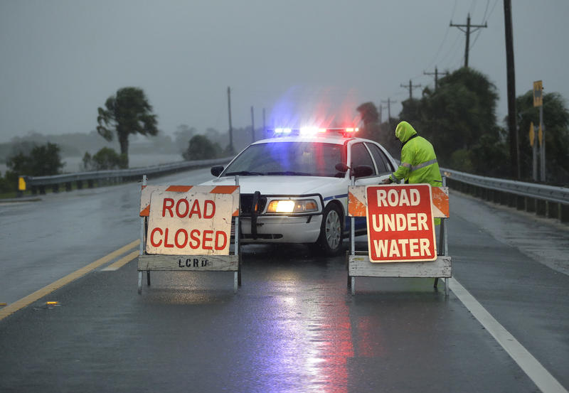 police block a road entering Cedar Key, Fla.