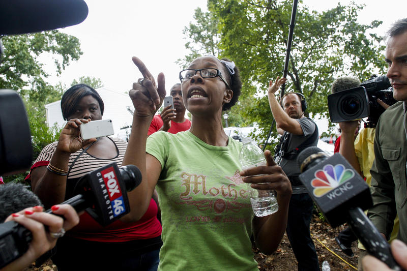 Taheshia Williams, center, tells her eyewitness account of the police shooting of Keith Lamont Scott, in Charlotte, N.C. Wednesday, Sept. 21, 2016. Scott's death on Sept. 20 led to protests and rioting.
