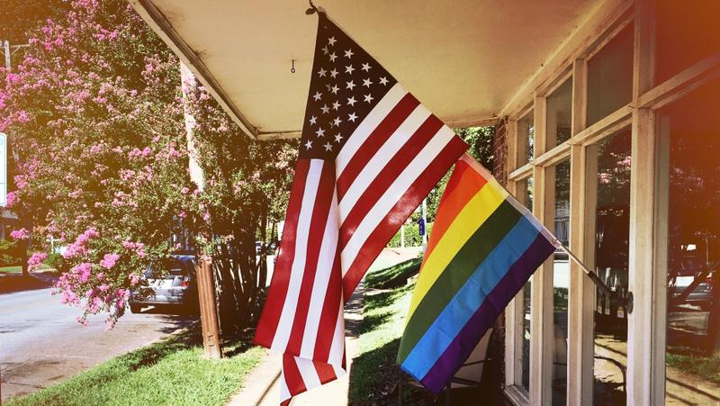 A photo of the American flag flying over a rainbow flag.