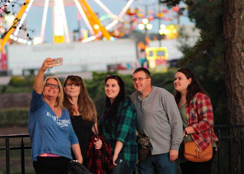 A family poses for a picture at the entrance on the opening night of the NC State Fair in Raleigh on Thursday, October 13, 2016.