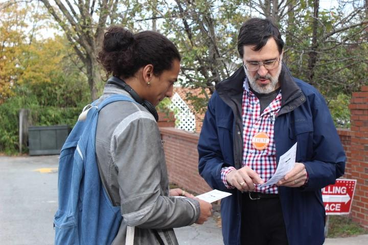 Orange County Democratic volunteer Paul Brinich explains the details of a Democratic sample ballot to UNC Chapel Hill student Ashaki George before George enters Chapel Hill First Baptist Church voting site to vote.