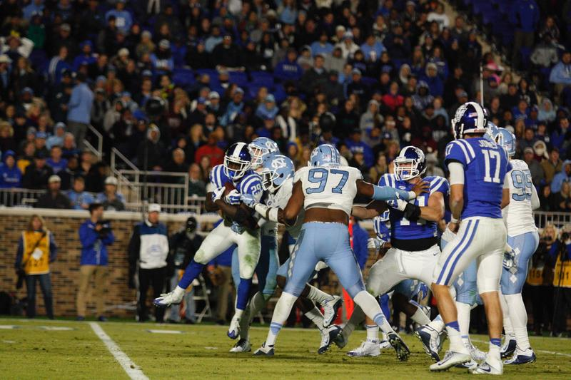 Mikey Bart and Marlon Dunlap of UNC tackle Shaun Wilson to end Duke's drive down the field.