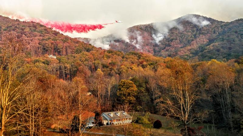 A heavy air tanker drops fire retardant over the Boteler Fire in western North Carolina