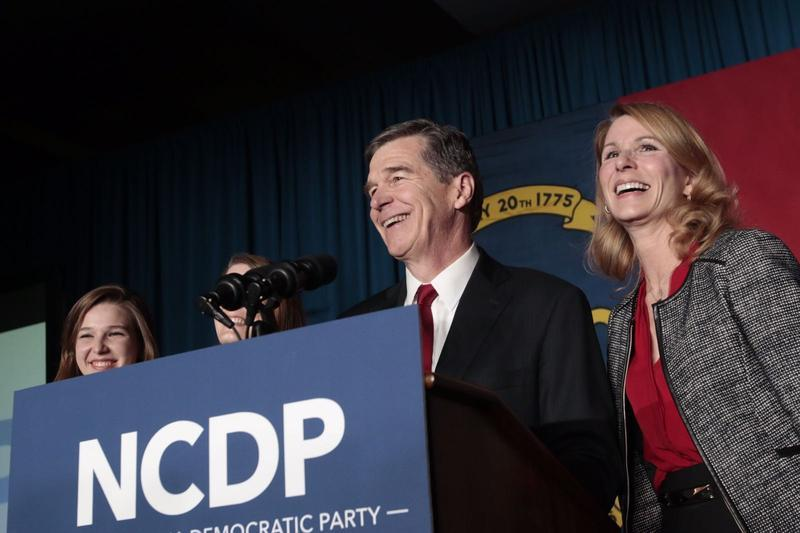 Roy Cooper at a podium with his wife, addresses his supporters in Raleigh. North Carolina gubernatorial candidates Cooper and incumbent Pat McCrory are locked in a tie with their race likely heading to a recount.