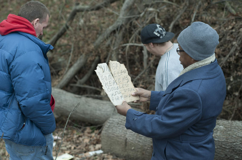 Chaplain Lynn Holloway inspects the sign of a homeless man at an outdoor camp