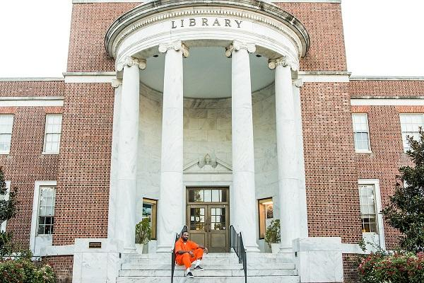 Sherrill Roland in front of the UNC-Greensboro library. Roland dons this orange jumpsuit while he's on campus as part of his public art project inspired by time he served in a District of Columbia jail for a crime he did not commit.