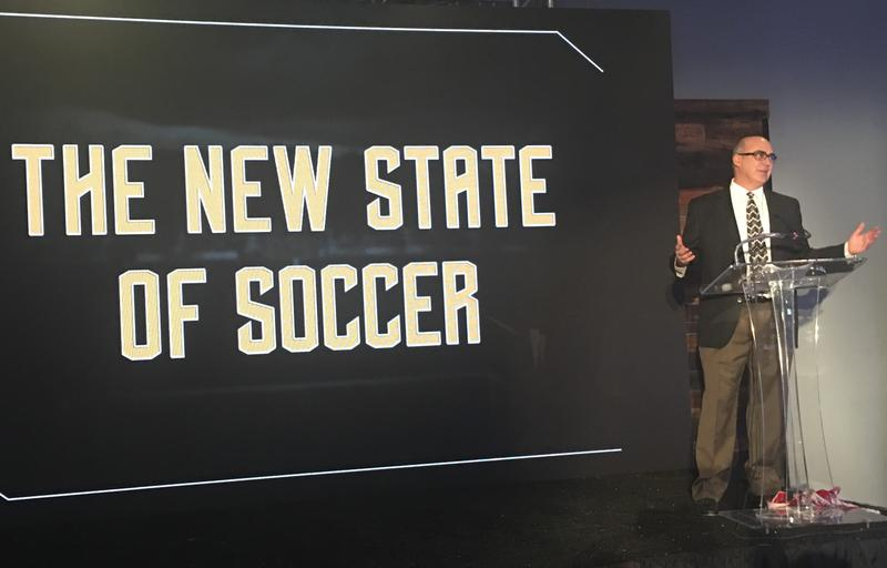 Steve Malik, owner of North Carolina FC, unveils the team's rebranded logo.